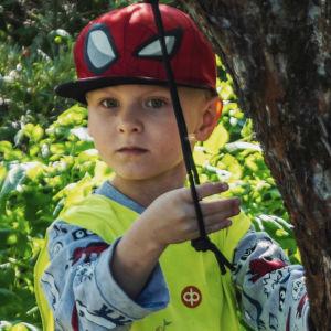 Liten pojke i gul reflexväst och röd skärmmössa står i en lummig trädgård och leker med ett rep som hänger från ett äppelträd.