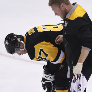 Sidney Crosby eskorteras av isen.