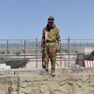 En talibankrigare övervakar platsen där bombdådet utanför Kabuls flygplats inträffade.