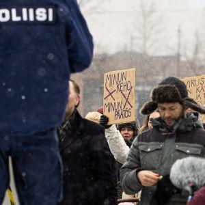 Poliiseja ja mielensosoittajia.