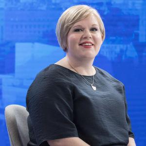 Annika Saarikko sitter på en stol vid ett bord. Framför henne finns ett glas vatten och en mikrofon. Bakgrunden består av en elektronisk duk som är blå.