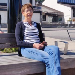 En äldre kvinna sitter på en bänk och ler utanför biblioteket i Nickby.