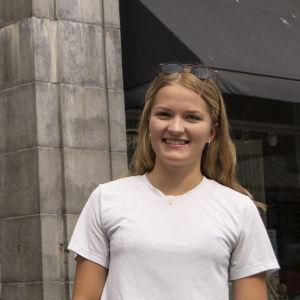 en ung kvinna i vit skjorta står utanför en byggnad
