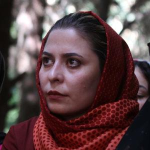 Tre afghanska kvinnor fotograferade från sidan. De tittar framåt.