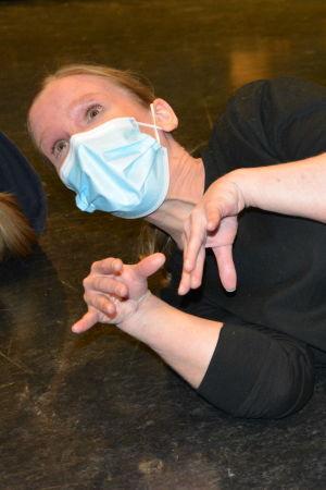 Lisa Taulio, en dam med svart tröja, jeans och ett ljusblått munskydd, ligger på en teaterscen med fingrarna utspärrade som en nyfödd kattunge.