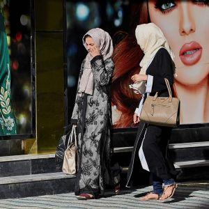 Två kvinnor går på en gata i Kabul bredvid en väggmålning med två kvinnor.