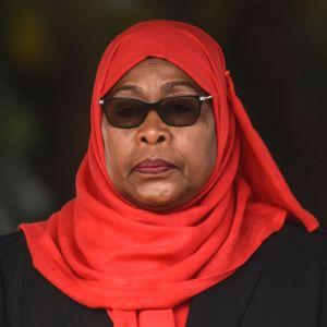 Samia Suluhu Hassan, svartklädd med klarröd sjal och mörka solglasögon.