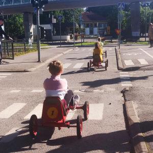 Barn på röd trampbil i övningslandskap för trafik, med övergångsställen, korsningar och trafikljus.