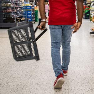En person som går omkring i en mataffärer med en korg i handen.