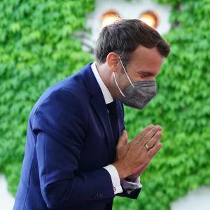 Emmanuel Macron och Angela Merkel står mittemot varandra. Macron gör en hälsning genom att buga och lägga ihop händerna med handflatorna mot varandra i brösthöjd.