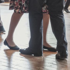 Fötter till dansande par. Parkettgolv.