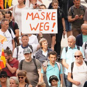 Folkmassa som demonstrerar. Det syns ett paraply och en skylt med tysk text.