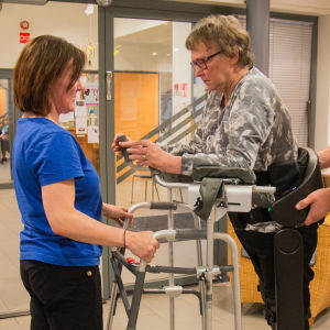 Maj-Len Sjöberg testar gångroboten Indego. Fysioterapeuterna Daniel Söderman och Katri Pihlaja-Kuhna assisterar.