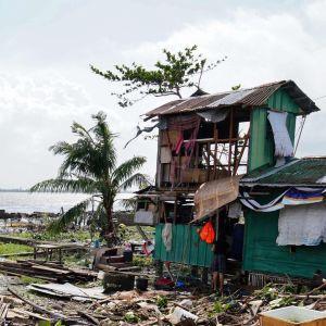 Bräder och skräp ligger på en strand efter tyfon i filippinerna.