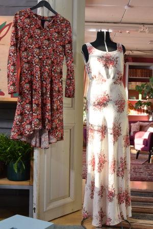 Ett vardagsrum där två klänningar är framlagda för uppvisning. Den ena klänningen är kort, med ett småblommigt rosa mönster på en brun botten, med lång ärm.