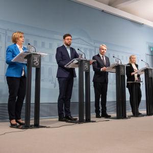 Foto på avstånd av fyra ministrar i presskonferens.