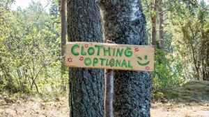 Kyltti jossa englanniksi teksti Clothing Optional eli suomeksi vaatetus vapaaehtoinen Natural High Healing Festivaalilla.