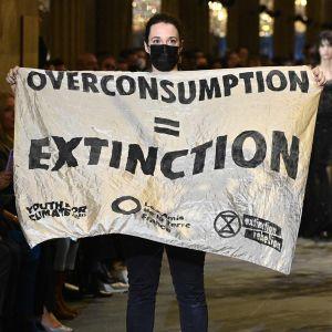 """Klimataktivisten höll upp en banderoll med budskapet """"överkonsumtion = utdöende"""", innan säkerhetsvakter bar bort henne."""