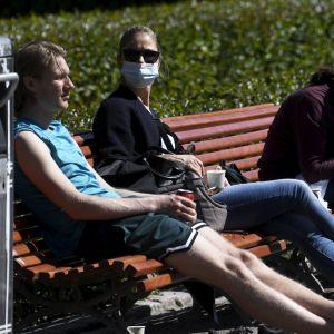 Bänkar fyllda med folk i Esplanadparken i Helsingfors.