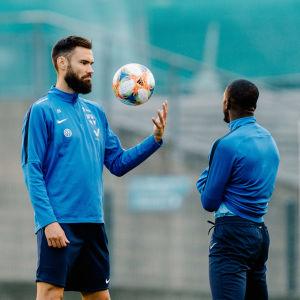 Tim Sparv och Glen Kamara diskuterar med varandra på fotbollsplanen.