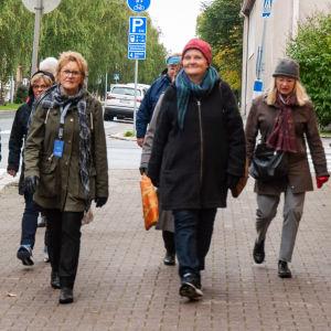 En grupp kvinnor vandrar på en stenlagd trottoar.