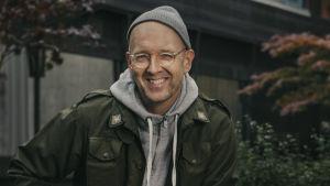 Författaren Johan Kling sittande ute på en mur. 2019.