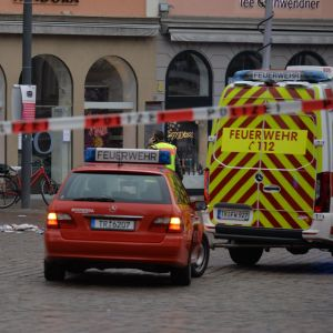 En polis står bakom polisband. I bakgrunden en brandbil och en ambulans.