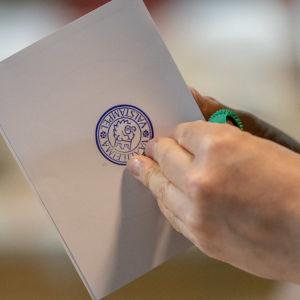 Person håller i en stämplad röstningsblankett.
