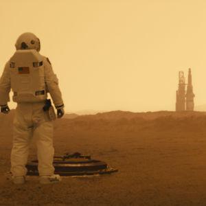 En astronaut på avstånd blickar ut över det karga Marslandskapet.