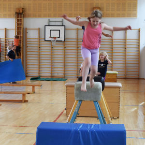 Barn som hoppar i gymnastiksal.