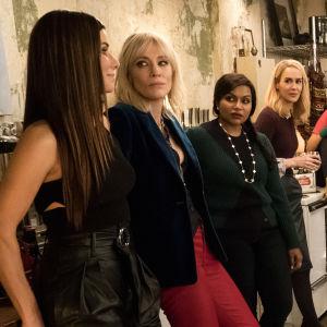 Debbie, Lou, Daphne, Amita, Tammy, Constance, Nine Ball och Rose Weil står samlade i ett kök och pratar med varandra.