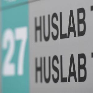 En skylt med texten Huslab Tullbommen och en pil och siffran 27.