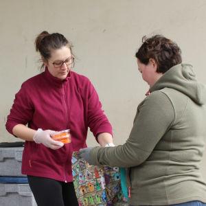 kvinna ger mat till en annan kvinna som har egen kass