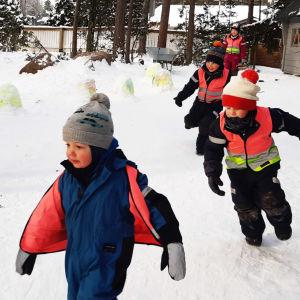 Barn som jagar varandra utomhus.