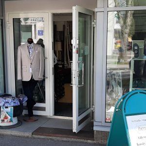 En affär vid en trottora. I skyltfönstret syns klänningar och herrkostymer. En skylt står på gatan utanför.