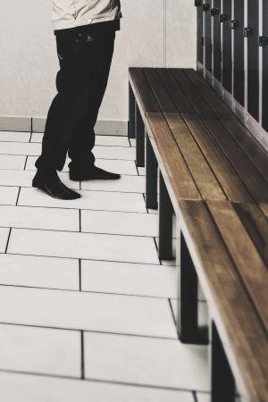Person i omklädningsrum. Bilden beskuren så att personen endast syns från midjan och nedåt.
