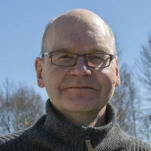 Flintskallig man med glasögon tittar in i kameran. Han har en grå tröja på sig och står utomhus.
