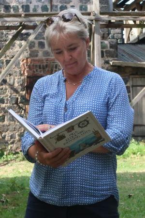 Carina Wolff-Brandt står bland gamla slaggstensbyggnader med boken uppslagen i händerna och läser ur boken.
