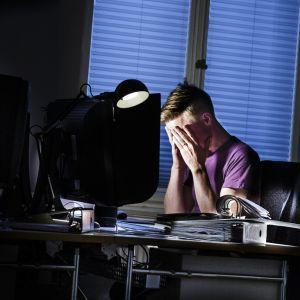 En person sitter i ett mörkt rum framför en dator. Han har huvudet i händerna och ser stressad ut.