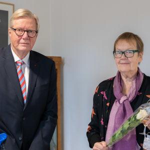 En man och en kvinna i festkläder tittar in kameran. Mannen har kryckor och kvinnan har en vit ros i famnen.