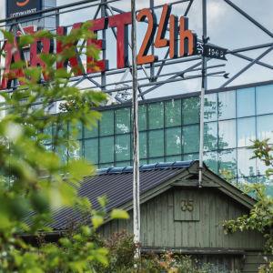 """I förgrunden äppelträd och en liten, gammal grönmålad stuga. I bakgrunden en stor glasvägg och stora, röda bokstäver med texten """"Citymarket 24h""""."""