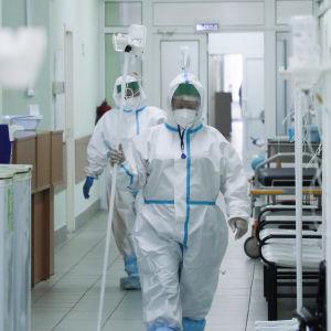 Två sjukskötare i skyddsutrustning går genom en korridor i ett sjukhus.