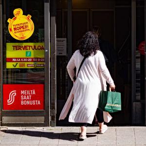 En kvinna på väg in genom dörren till en livsmedelsaffär.