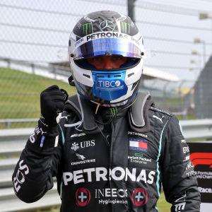 Valtteri Bottas höjer näven framför Lewis Hamilton.