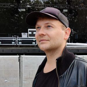 Daniel Lindholm utomhus framför en tom scen.