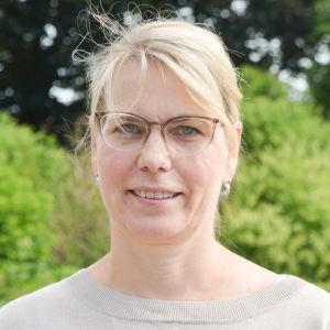 Johanna Tamminen utomhus i en grön miljö i beige tröija.