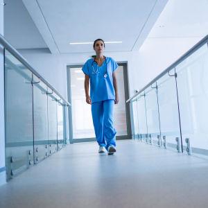 En sjukskötare fotograferad nerifrån medan hon går i en sjukhuskorridor.