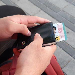 Händer som håller i plånbok med identitetshandlingar.