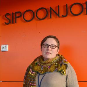 kvinna framför orange vägg