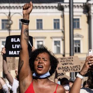 En kvinna i röd topp håller upp knytnäven under Black Lives Matter-demonstrationen.